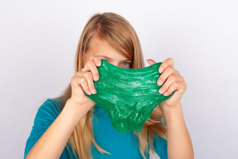 Schoolmeisje die een groen slijm voor haar gezicht houden royalty-vrije stock foto's