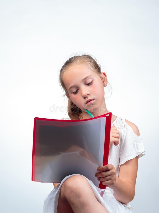 Schoolmeisje die een notastootkussen bekijken terwijl het houden van een potlood royalty-vrije stock foto's