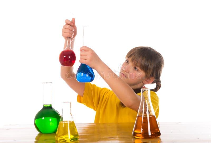 Schoolmeisje die het experiment van de chemiewetenschap doen stock afbeeldingen