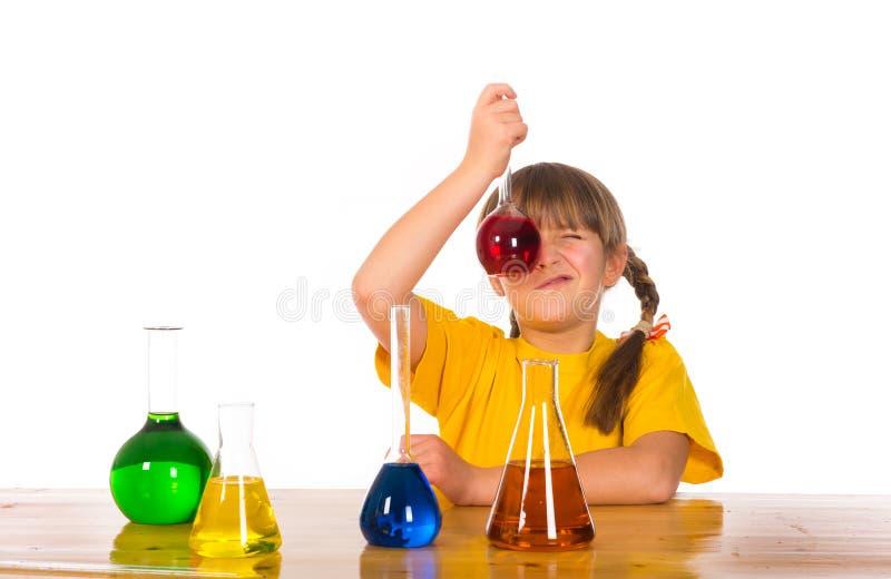 Schoolmeisje die het experiment van de chemiewetenschap doen stock afbeelding