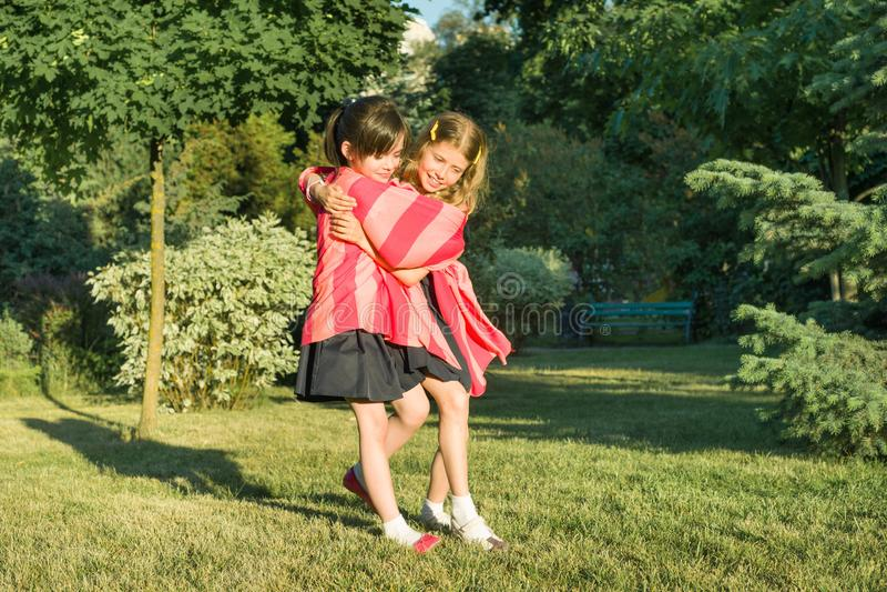 Schoolmeisje 7 die, 8 jaar van twee meisjevrienden het spelen op de weide in het park omhelzen royalty-vrije stock fotografie