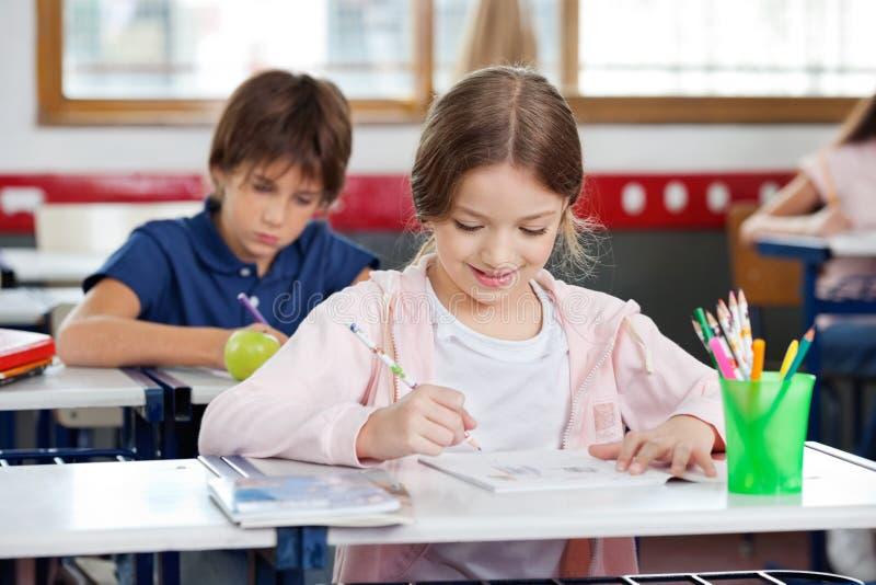 Schoolmeisje die terwijl het Trekken in Klaslokaal glimlachen stock foto's