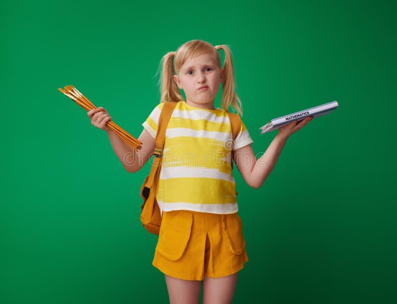 Schoolmeisje die die tussen wetenschappen en kunst kiezen op groen worden geïsoleerd royalty-vrije stock fotografie