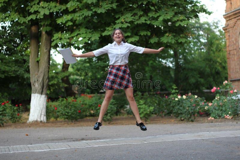 Schoolmeisje die voor vreugde springen stock fotografie