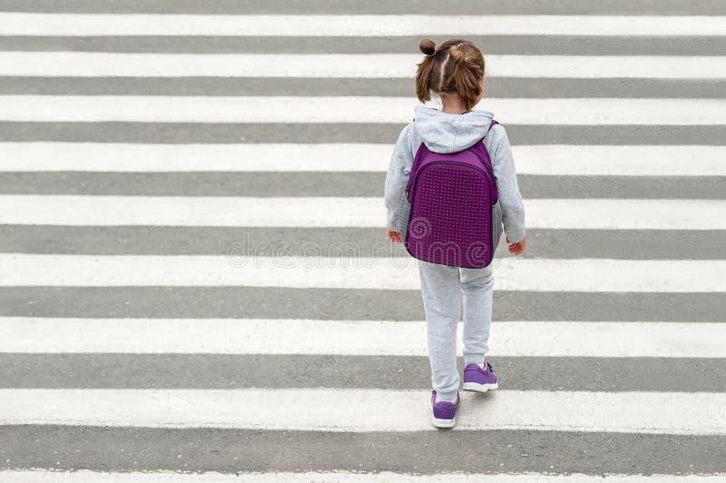 Schoolmeisje die weg op manier kruisen aan school De gestreepte manier van de verkeersgang in de stad Conceptenvoetgangers die ee stock foto