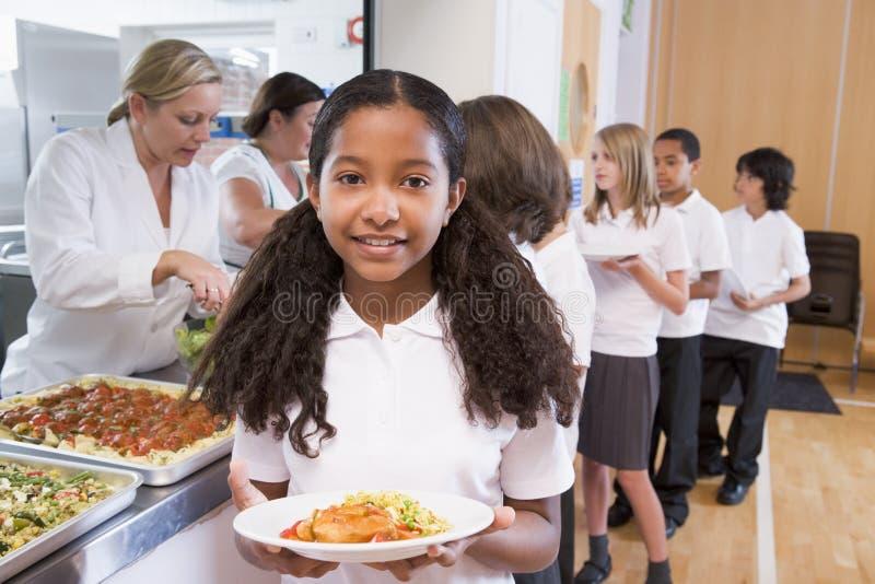 Schoolmeisje in een schoolcafetaria stock foto's