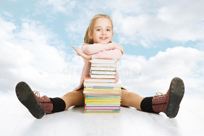 Schoolmeisje en boekenstapel. Glimlachende gelukkige kindleerling royalty-vrije stock afbeeldingen