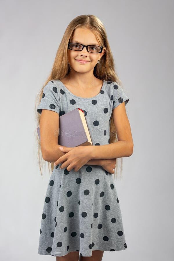 Schoolmeisje in glazentribunes met een boek in haar handen stock afbeeldingen