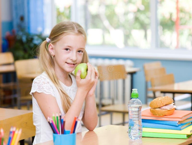Schoolmeisje in het klaslokaal die een groene appel eten royalty-vrije stock foto's