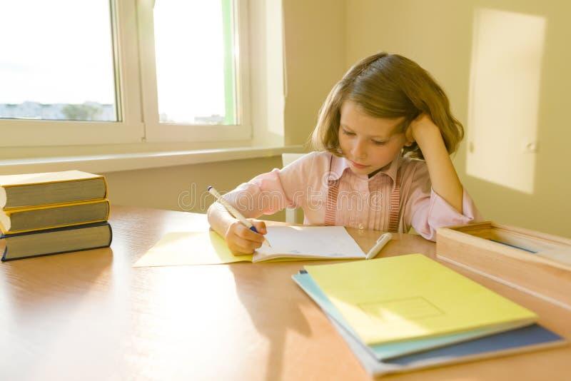 Schoolmeisje, meisje die van 8 jaar, bij lijst met boeken zitten en in notitieboekje schrijven School, onderwijs, kennis en kinde royalty-vrije stock fotografie