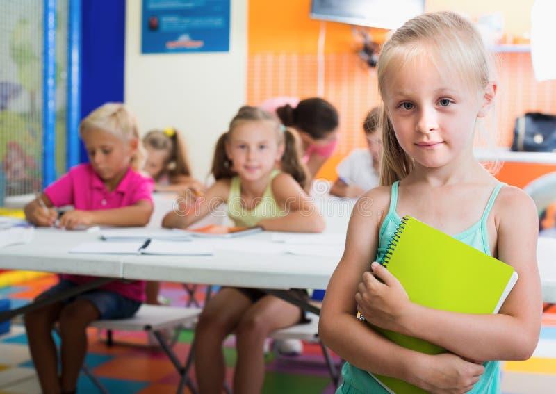 Schoolmeisje met blocnote in basisschoolklasse binnen royalty-vrije stock afbeeldingen