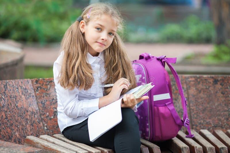 Schoolmeisje met een rugzak en een boek in openlucht Onderwijs en het leren concept stock fotografie