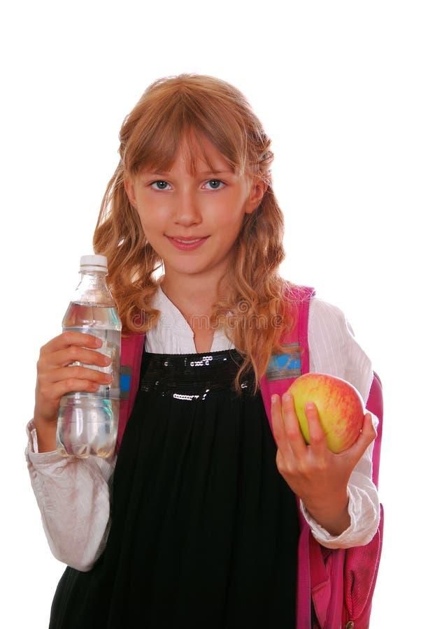 Schoolmeisje met fles van water en een appel stock foto's