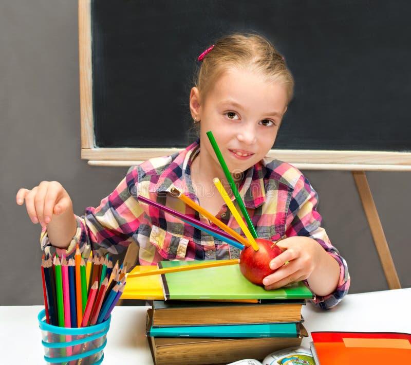 Schoolmeisje met kleurpotloden en appel royalty-vrije stock afbeelding