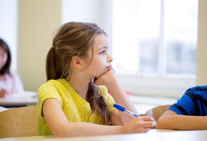Schoolmeisje met pen die in klaslokaal bored stock foto's