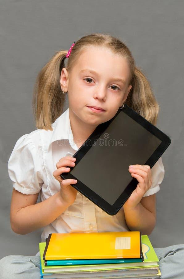 Schoolmeisje met voorbeeldenboeken en tablet. royalty-vrije stock fotografie