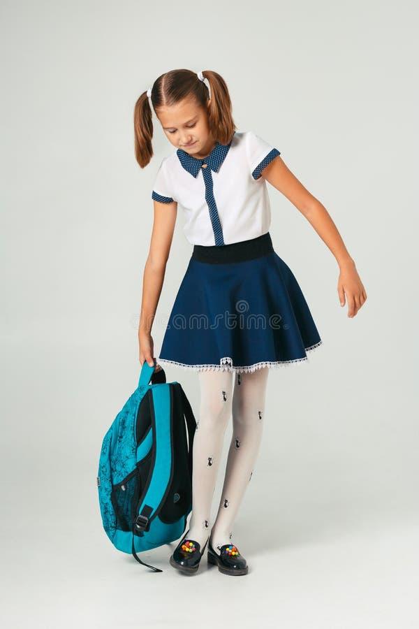 Schoolmeisje in school eenvormige holding een zware rugzak Het probleem om studententoebehoren te wegen stock foto