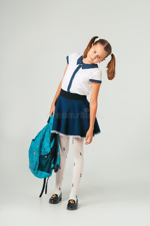 Schoolmeisje in school eenvormige holding een zware rugzak Het probleem om studententoebehoren te wegen royalty-vrije stock afbeeldingen