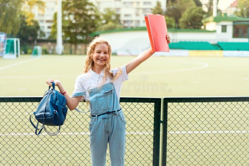 Schoolmeisjeblonde die met blauwe ogen een rode omslag en een rugzak houden stock foto's