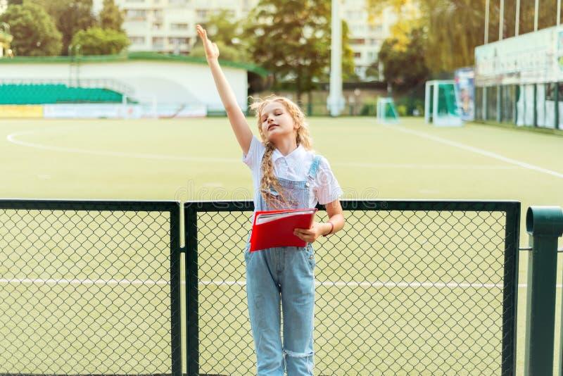Schoolmeisjeblonde en verhogingen haar hand omhoog royalty-vrije stock afbeelding