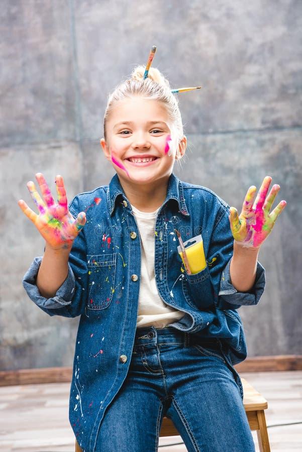 Schoolmeisjekunstenaar met geschilderd gezicht die palmen in verf en het glimlachen tonen royalty-vrije stock afbeelding