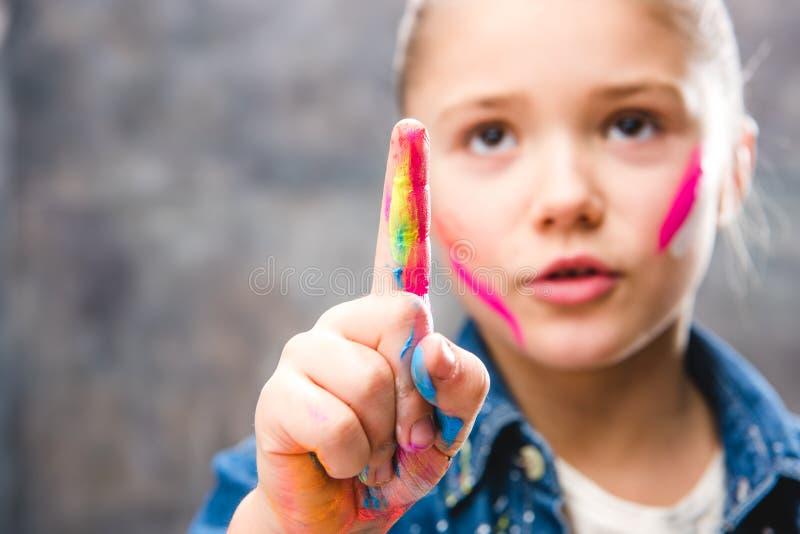 Schoolmeisjekunstenaar met geschilderd gezicht die met vinger richten stock illustratie