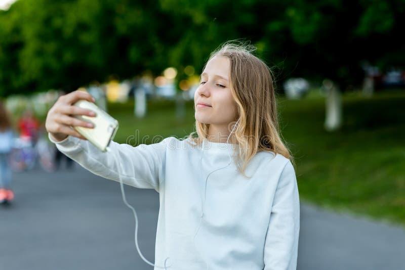 Schoolmeisjemeisje in de zomer bij park in straat In zijn hand houdt een smartphone nemend beelden van zich op de telefoon stock afbeeldingen