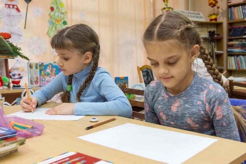 Schoolmeisjes bij hun bureaus in tekeningsklasse stock afbeeldingen