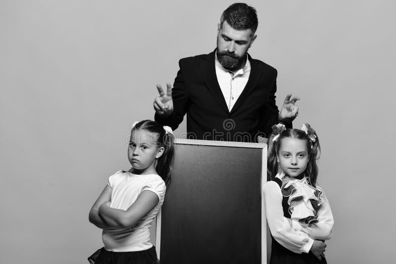Schoolmeisjes dichtbij bord en kerel op gele achtergrond Terug naar het Concept van de School Meisjes en mens met ernstige gezich royalty-vrije stock foto
