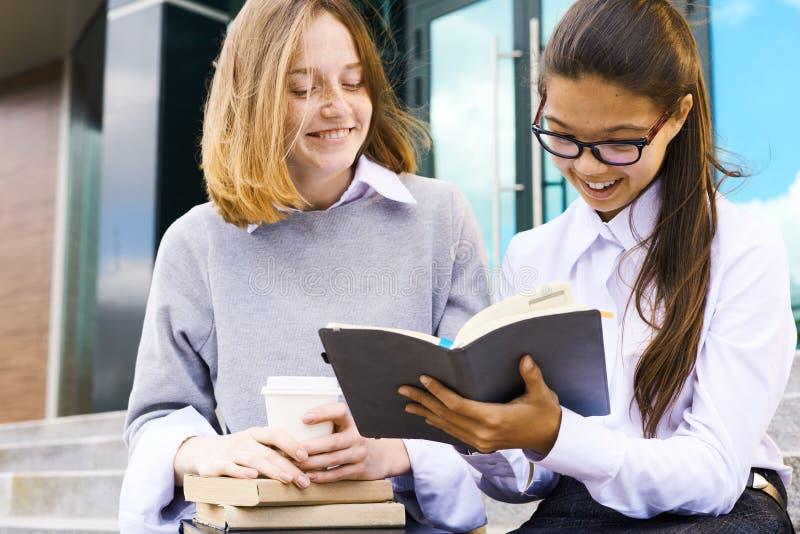 Schoolmeisjes die Boek in openlucht lezen royalty-vrije stock afbeeldingen