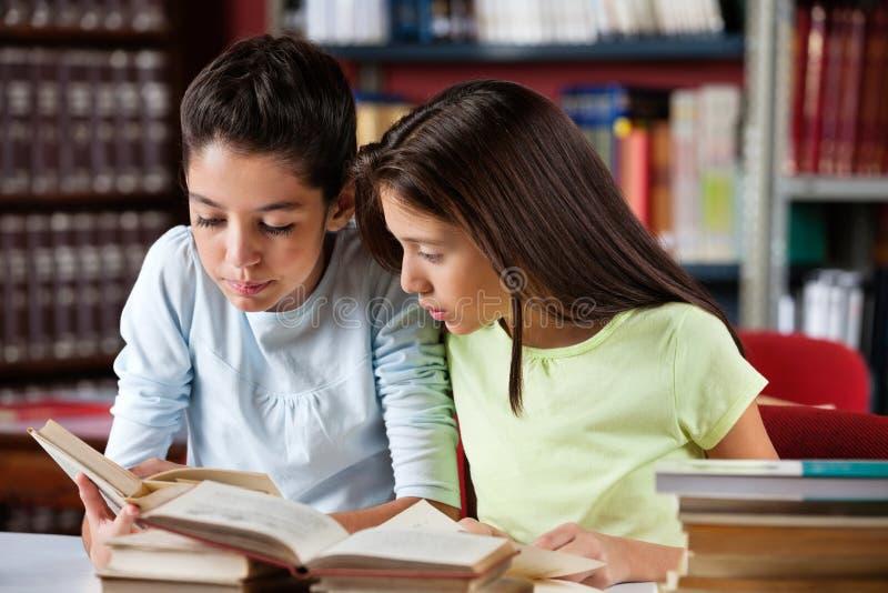 Schoolmeisjes die Boek samen in Bibliotheek lezen royalty-vrije stock foto
