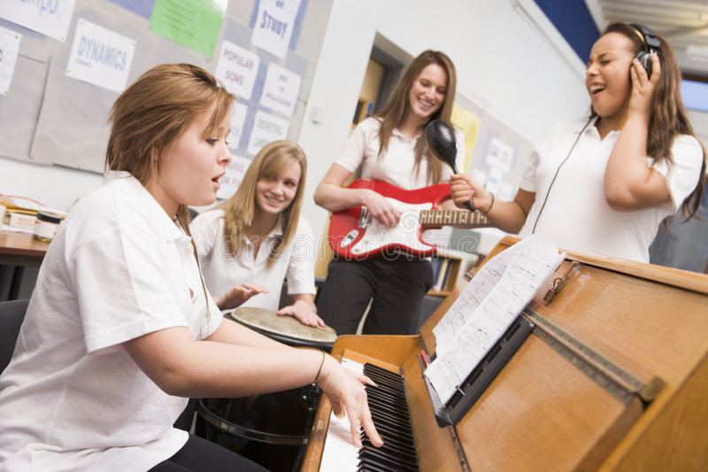 Schoolmeisjes die muzikale instrumenten spelen stock foto's