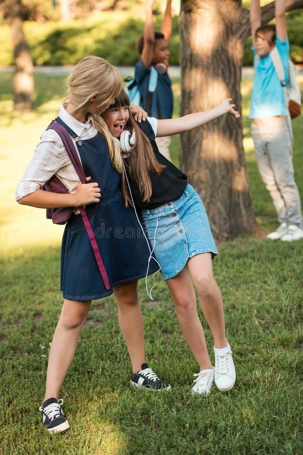 Schoolmeisjes met rugzakken in park royalty-vrije stock foto