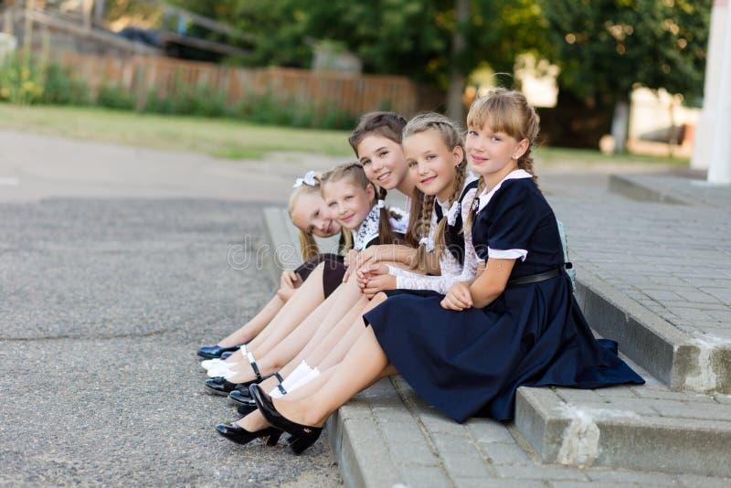 Schoolmeisjes in school eenvormige rust op een onderbreking dichtbij de school stock foto's