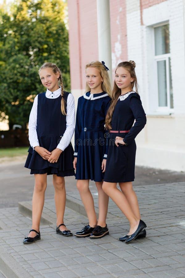Schoolmeisjes in school eenvormige rust op een onderbreking dichtbij de school stock foto