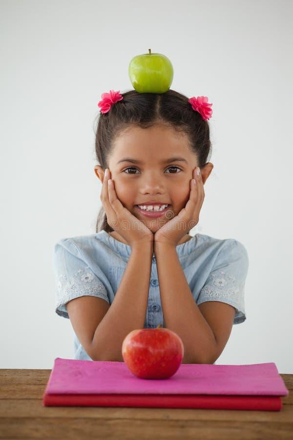 Schoolmeisjezitting met groene appel op haar hoofd tegen witte achtergrond stock afbeelding