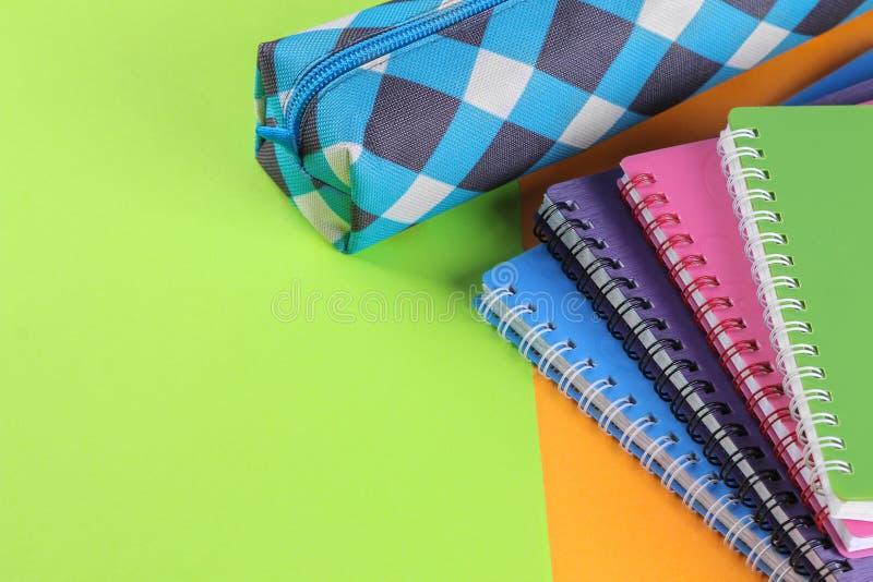 Schoolnotitieboekjes van verschillende kleuren en een potloodgeval op een heldere oranje en groene achtergrond De levering van de royalty-vrije stock foto's