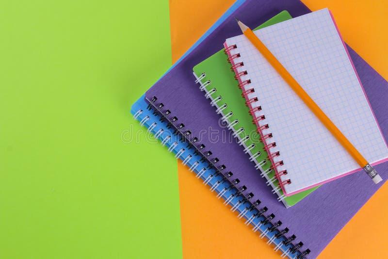 Schoolnotitieboekjes van verschillende kleuren op een heldere oranje en groene achtergrond De levering van de school stock afbeelding