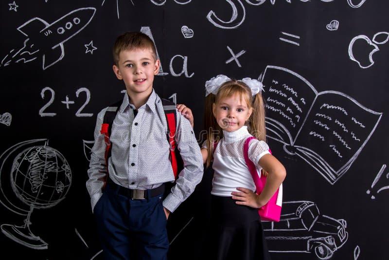 Schoolpartners, jongen en meisje, die zich vóór het bord als achtergrond met een rugzak op hun ruggen bevinden teleurgesteld royalty-vrije stock afbeeldingen