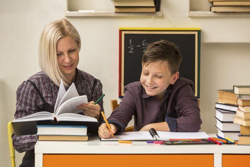 Schoolprivé-leraar met jonge student helping stock afbeelding