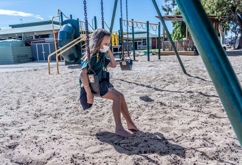 Schools closures Coronavirus lockdown. Bored school kid alone in playground feeling sad and lonely. Covid-19 outbreak schools closures. Sad Schoolgirl with face royalty free stock photo