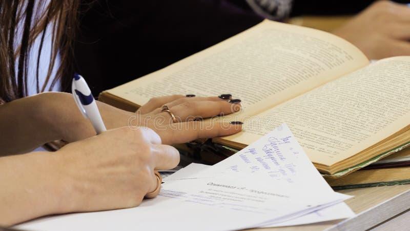 Schoolstudent ` die s examen het schrijven antwoord in klaslokaal voor onderwijs en geletterdheidsconcept nemen De jonge vrouweli royalty-vrije stock fotografie