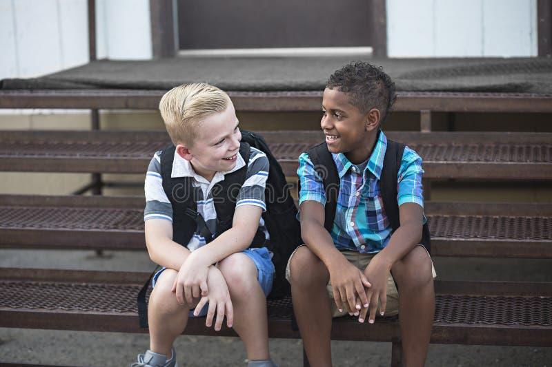 Schoolstudenten die samen terwijl het zitten op de treden op school spreken stock fotografie