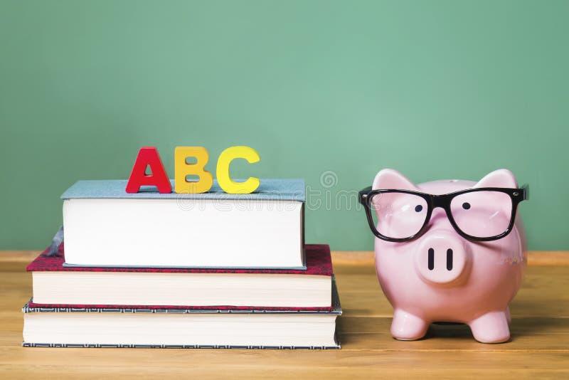 Schoolthema met ABCs en roze spaarvarken met bord op de achtergrond stock foto's