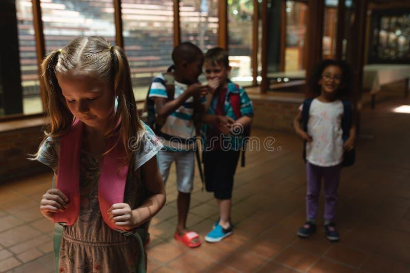 Schoolvrienden die een droevig meisje in gang van basisschool intimideren royalty-vrije stock afbeelding