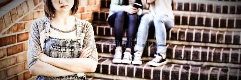 Schoolvrienden die een droevig meisje in schoolgang intimideren royalty-vrije stock afbeeldingen