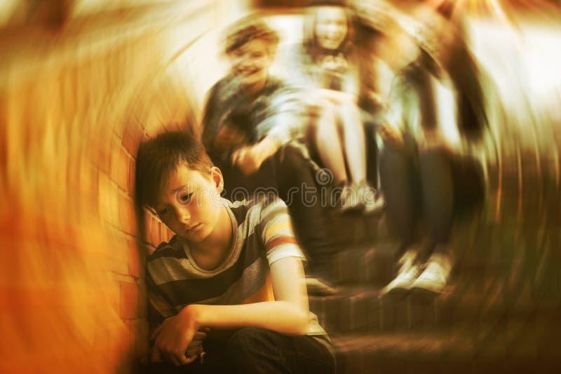 Schoolvrienden die een droevige jongen in schoolgang intimideren royalty-vrije stock fotografie