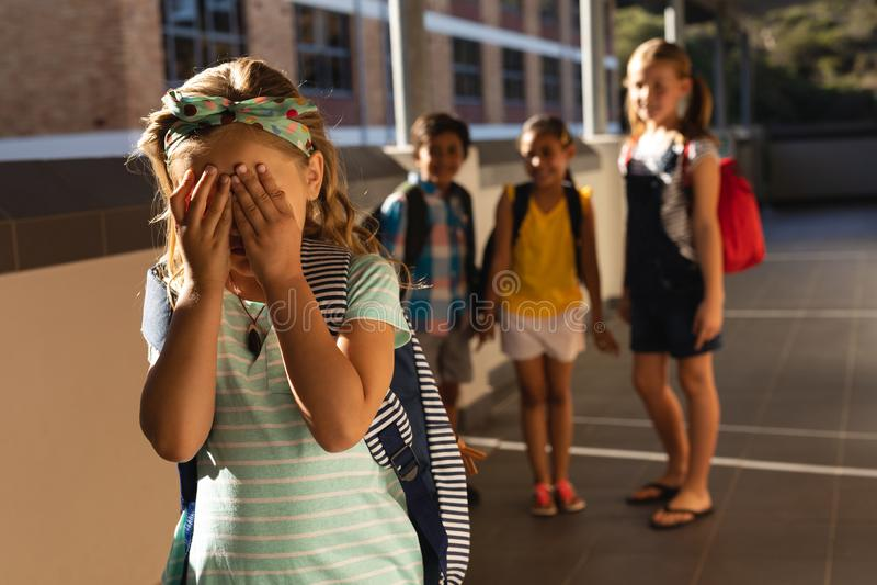 Schoolvrienden die een schreeuwend meisje in gang van basisschool intimideren royalty-vrije stock foto