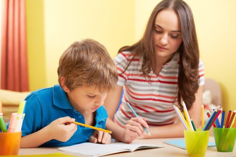 Schoolwork met moeder stock foto
