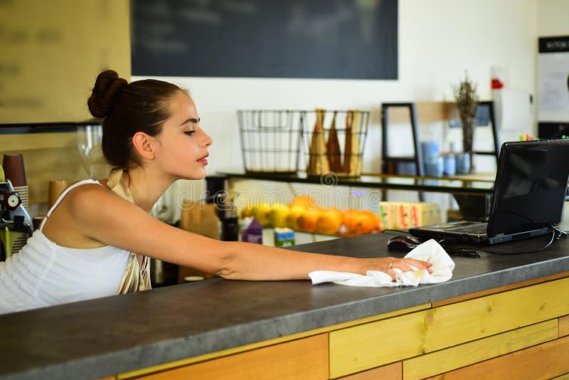 Schoon afvegen Vrouwenbarista in koffiewinkel Barista schone tegenbovenkant in bar Mooie vrouwentribune achter koffieteller royalty-vrije stock afbeeldingen